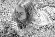 El niño disfruta de la fragancia del tulipán mientras que miente en el prado Concepto de la alergia La muchacha en cara feliz sos fotos de archivo libres de regalías
