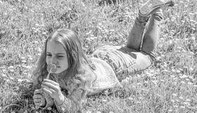 El niño disfruta de la fragancia del tulipán mientras que miente en el prado Concepto de la alergia Muchacha con el pelo largo qu fotografía de archivo libre de regalías