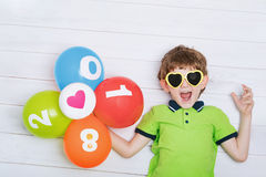 El niño divertido con las gafas de sol, sosteniendo los globos del arco iris miente en el th Imagenes de archivo