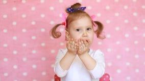 El niño divertido envía beso El niño dulce de la niña envía besos del aire Fondo rosado metrajes