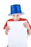 El niño divertido feliz hermoso que lleva el sombrero azul del partido sostiene una bandera blanca rectangular Imagen de archivo libre de regalías