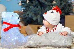 El niño divertido mira un oso Navidad Año Nuevo Fotos de archivo libres de regalías