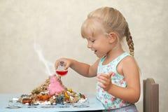 El niño divertido por un hogar hizo el volcán fotos de archivo