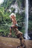 El niño divertido se sienta en gancho debajo de la cascada en selva tropical fotografía de archivo libre de regalías