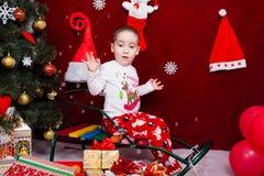 El niño divertido se sienta en un trineo al lado de un árbol de navidad Fotografía de archivo libre de regalías