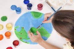 El niño drena el globo coloreado de las pinturas Imagen de archivo