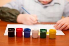 El niño drena las pinturas del cuadro Imagen de archivo