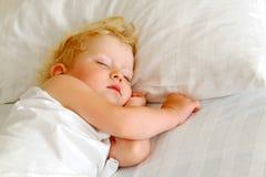 El niño duerme en cama Fotos de archivo libres de regalías