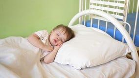 El niño duerme en la sala de hospital concepto de niño durmiente el bebé encantador se cae dormido en la cama blanca en su cama imágenes de archivo libres de regalías