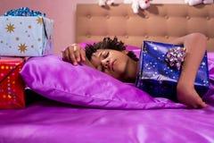 El niño durmiente abraza la caja de regalo imagen de archivo libre de regalías