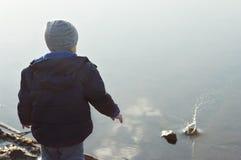 El niño echó una piedra en el agua Fotografía de archivo libre de regalías