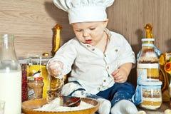El niño el cocinero cocina la comida en cocina Fotos de archivo libres de regalías