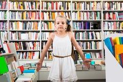 El niño elegante de la muchacha pasmó muchos libros en una librería Foto de archivo