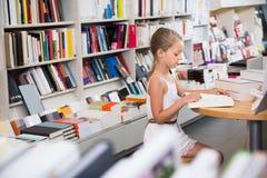 El niño elegante de la muchacha se involucra con un libro en la biblioteca Fotos de archivo libres de regalías