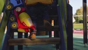 El niño elegante rubio caucásico juega en diapositiva con el camión del juguete almacen de metraje de vídeo