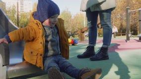 El niño elegante rubio caucásico juega en diapositiva almacen de metraje de vídeo