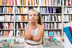 El niño elegante rubio de la muchacha pasmó muchos libros en una librería Fotos de archivo libres de regalías