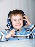 El niño en auriculares imagen de archivo