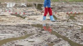 El niño en botas camina en el charco de la suciedad, cuidado de la inseguridad de los niños metrajes