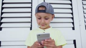 El niño en casquillo y camiseta está sosteniendo un smartphone delante de él y concentrado jugando al videojuego, en un blanco almacen de metraje de vídeo