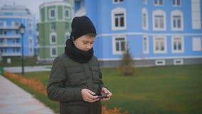 El niño en chaqueta gris oscuro caliente y casquillo y bufanda negros está jugando el teléfono que se coloca en la calle con los  almacen de video