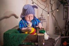 El niño en el casquillo del ratón juega un pyromid de madera Imagenes de archivo