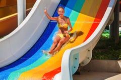 El niño en el tobogán acuático en la demostración del aquapark manosea con los dedos para arriba Foto de archivo
