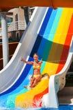 El niño en el tobogán acuático en la demostración del aquapark manosea con los dedos para arriba Imagenes de archivo