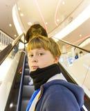 El niño en escalera móvil parece seguro de sí mismo Imagen de archivo libre de regalías