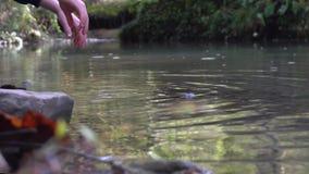 El niño en gomas entra en un río de la montaña, moja sus manos y sacude apagado el agua almacen de video