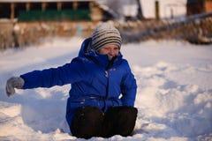 El niño en invierno viste fuera de la ciudad en el fondo de a fotografía de archivo