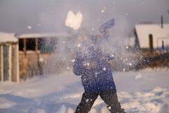 El niño en invierno viste fuera de la ciudad en el fondo de a imagenes de archivo