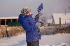 El niño en invierno viste fuera de la ciudad en el fondo de a fotografía de archivo libre de regalías