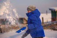 El niño en invierno viste fuera de la ciudad en el fondo de a foto de archivo