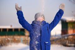 El niño en invierno viste fuera de la ciudad en el fondo de a foto de archivo libre de regalías