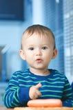 El niño en la cocina con la salchicha Fotografía de archivo libre de regalías