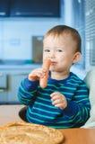 El niño en la cocina con la salchicha Fotos de archivo libres de regalías