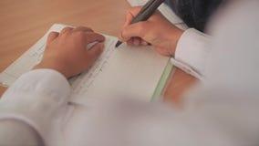 El niño en la lección de deletreo escribe palabras en un cuaderno Visión desde el hombro del muchacho