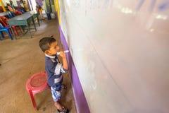 El niño en la lección en la escuela del camboyano del proyecto embroma cuidado Imagen de archivo libre de regalías
