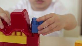 El niño en la tabla juega con un coche del juguete y bloques coloreados Desarrollo infantil metrajes