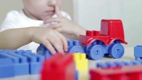 El niño en la tabla juega con un coche del juguete y bloques coloreados Desarrollo infantil almacen de metraje de vídeo