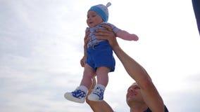 El niño en las manos del papá en fondo del cielo azul, bebé feliz asoma debajo del cielo claro, niño en manos fuertes del ` s del metrajes