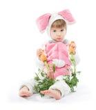 El niño en liebres del conejito viste sostener zanahorias Foto de archivo libre de regalías