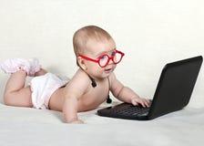 El niño en los vidrios con los auriculares en el cuello que mira la exhibición del ordenador portátil Imagen de archivo libre de regalías