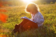 El niño en el otoño Una muchacha con un libro se está sentando en la hierba en el sol en la puesta del sol imagen de archivo