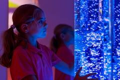 El niño en sitio estimulante sensorial de la terapia, snoezelen Niño que obra recíprocamente con la lámpara coloreada del tubo de fotografía de archivo libre de regalías