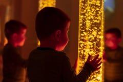 El niño en sitio estimulante sensorial de la terapia, snoezelen Niño que obra recíprocamente con la lámpara coloreada del tubo de fotografía de archivo