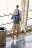 El niño en sus padres lleva a hombros la mirada hacia fuera de un viento brillante del aeropuerto Fotografía de archivo