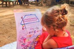 El niño en un café al aire libre lee el menú foto de archivo