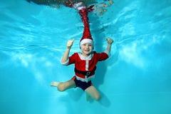 El niño en un casquillo y vestido como Santa Claus nada y presenta bajo el agua en un fondo azul, mirando la cámara y la sonrisa  fotos de archivo